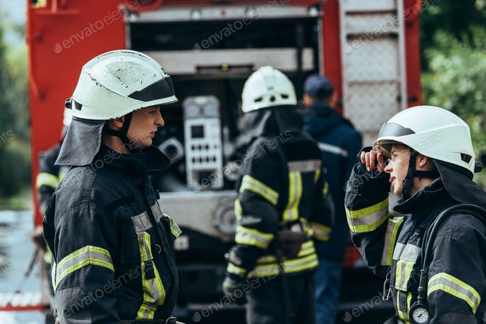 selective focus of firefighters having conversation while brigade standing at fire truck on street