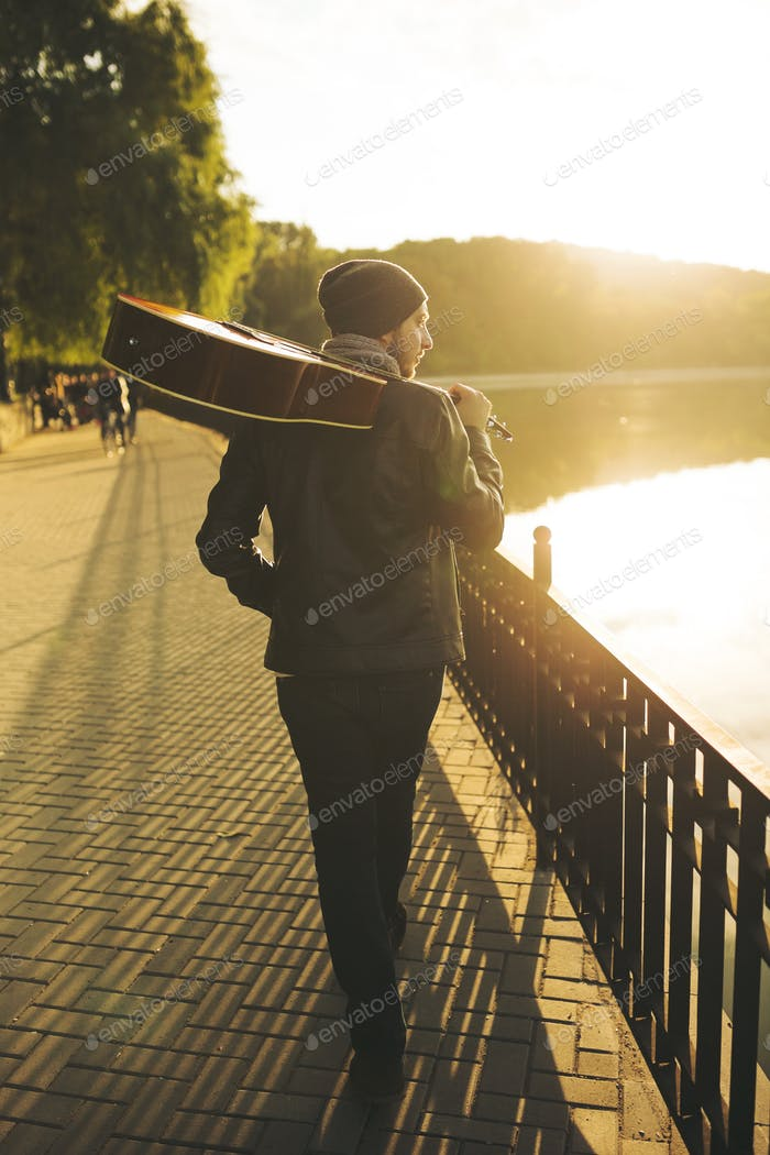 Young man walks by the lake and holding guitar