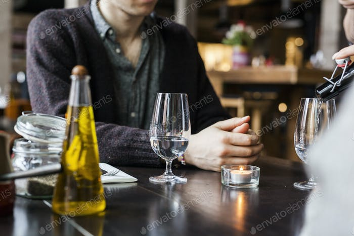 Midsection of man sitting at table in restaurant
