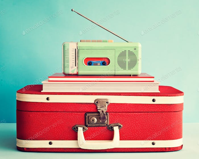 Vintage radio over books and antique suitcase