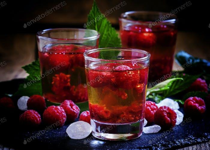 Alkoholischer Cocktail mit starkem Alkohol, Sirup und frischen Himbeeren