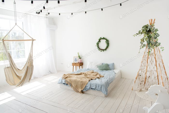 Stylish, trendy interior in Scandinavian style. In white loft room, there is wigwan macrame