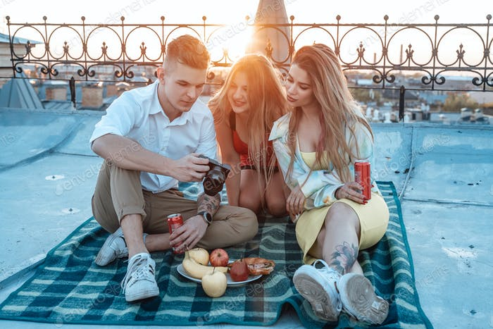 Two women and guy looking at photocamera