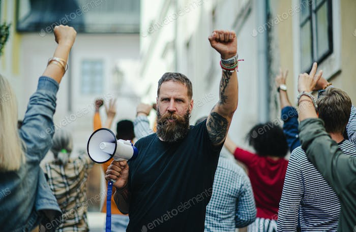 Portrait of man with megaphone protesting on streets, strike and demonstration concept
