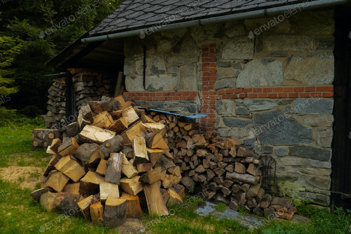 pile of fuel firewood stacked in front of a house