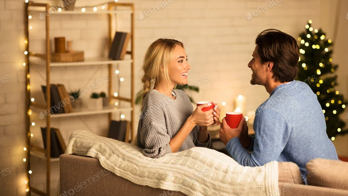 Christmas eve. Cute couple in love drinking hot tea