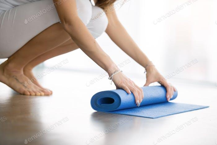 Close up of female hands unrolling yoga mat