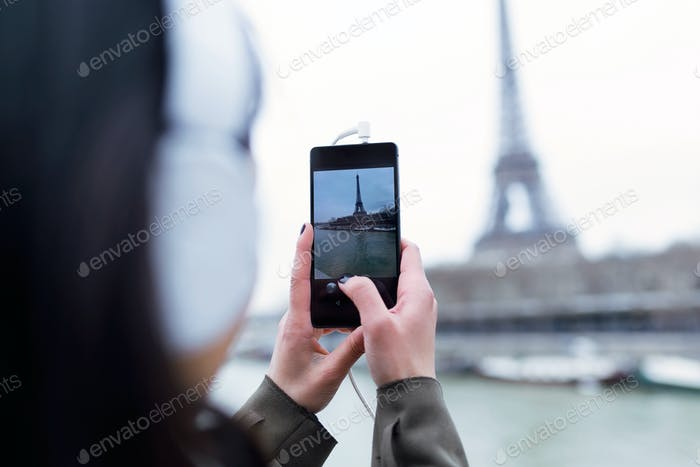 Back view of woman taking photograph of Eiffel tower from the ri