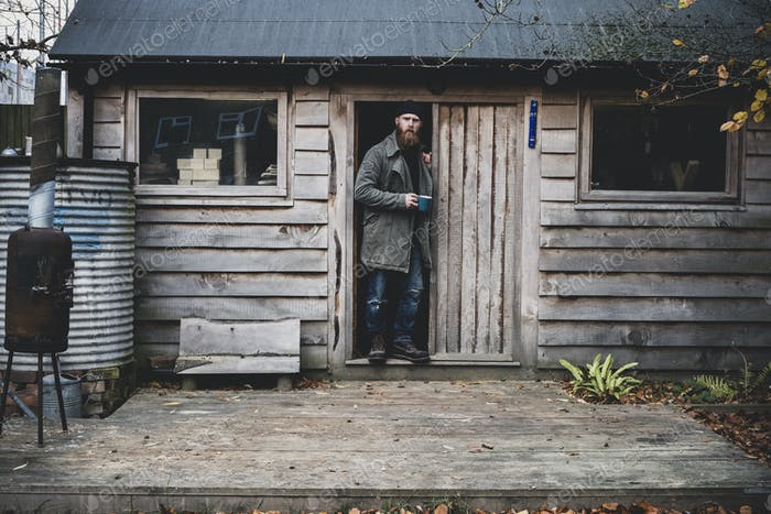 Bearded man standing in doorway of wooden workshop, holding blue mug, looking at camera.