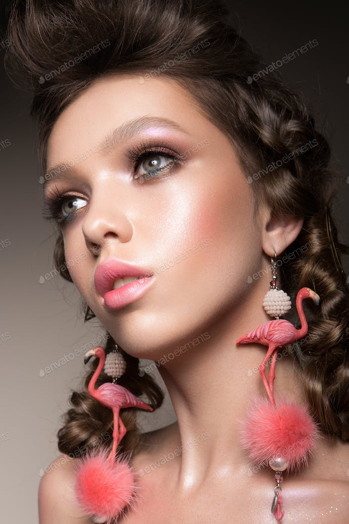 Glamour portrait of beautiful girl model with makeup and romantic hairstyle.
