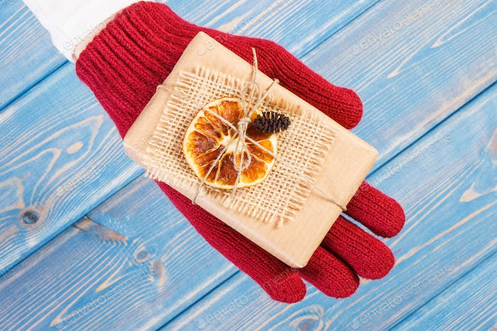 Hand of woman in woolen gloves with decorated gift for Christmas or other celebration