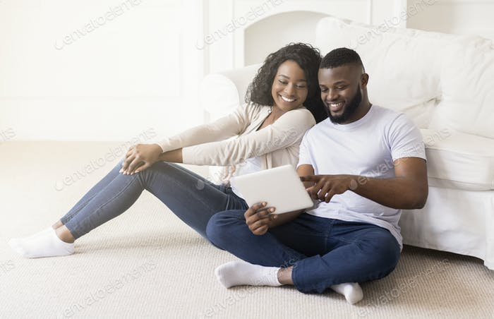 Cheerful couple using digital tablet together while sitting at home
