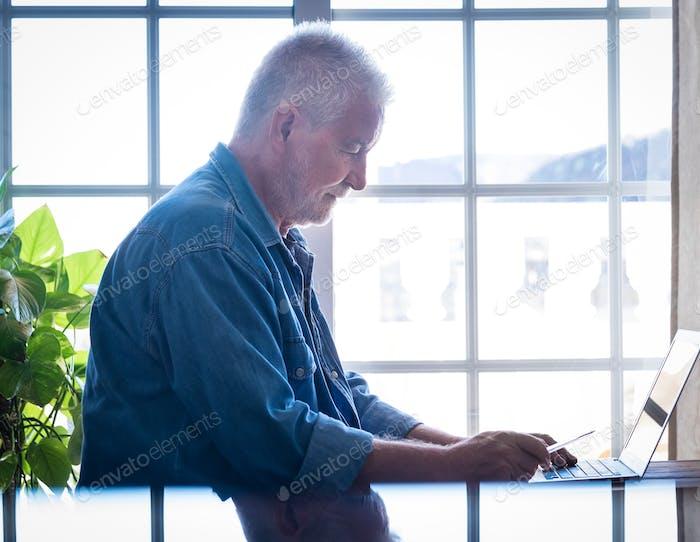 Hombre mayor concentrado que trabaja con un ordenador portátil en casa, las personas mayores modernas que utilizan tecnología inalámbrica