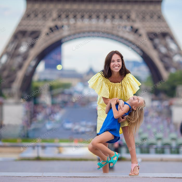 Happy family in Paris near Eiffel Tower during summer french vacation