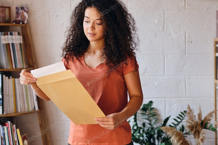 Beautiful woman in T-shirt dreamily opening envelope with exam results with bookshelf on background