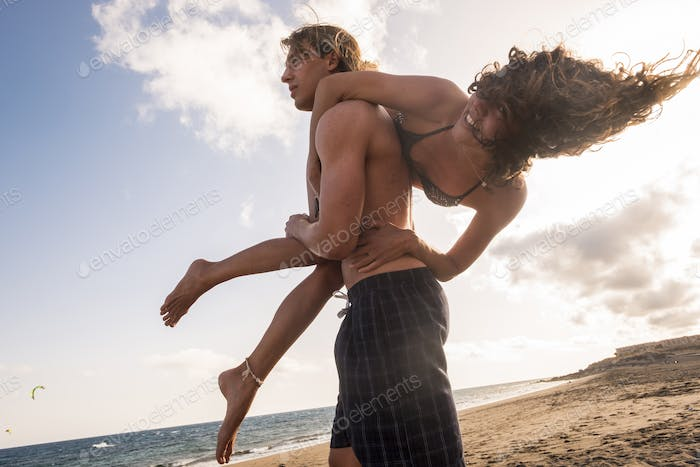 Nice couple of young people enjoy the beach and vacation time in summer together playing