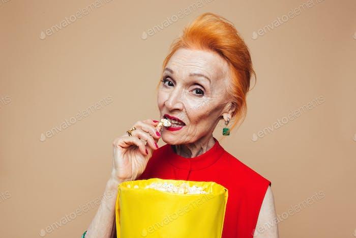 Amazing mature redhead fashion woman eating popcorn