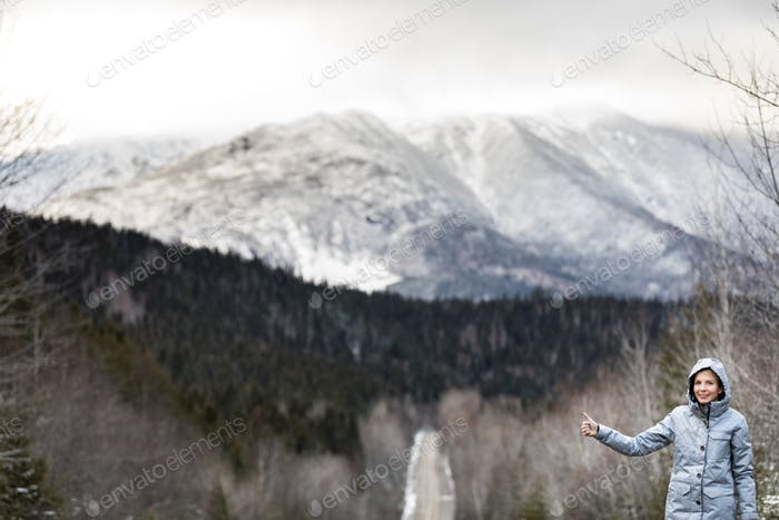 Woman Hitchhiking on a Winter Road with Beautiful Snowy Mountain