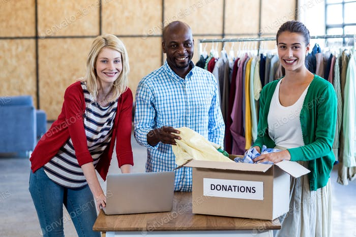 Kollegen Sortieren Kleidung aus Spendenbox
