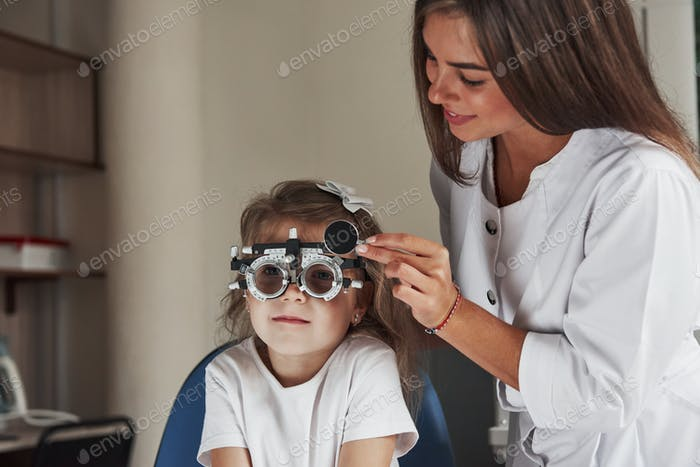 Doctor is tuning the device. Little girl in glasses sitting in clinic and having her eyes tested