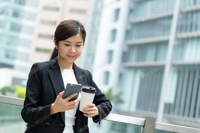 Businesswoman sending message with smartphone