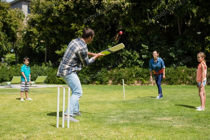 Happy family playing cricket in park