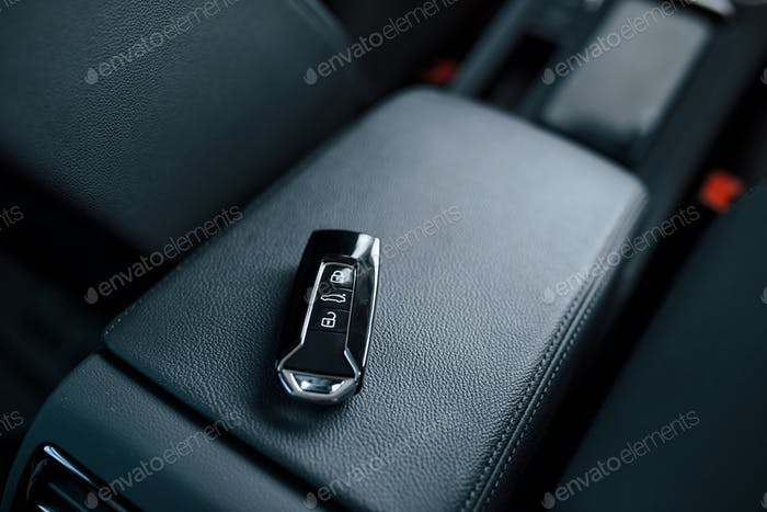 Einzelnes Objekt. Nahaufnahme von Schlüsseln, die im brandneuen, modernen Auto liegen