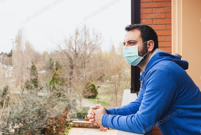 Junge Kaukasier mit Maske Blick auf die Terrasse.