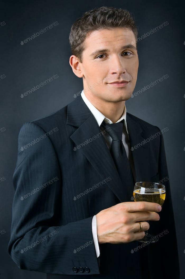 Portrait of a beautiful man with a glass of champagne
