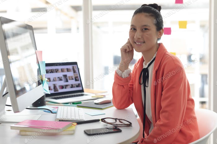 Front view of beautiful Asian female graphic designer looking at camera on desk in a modern office