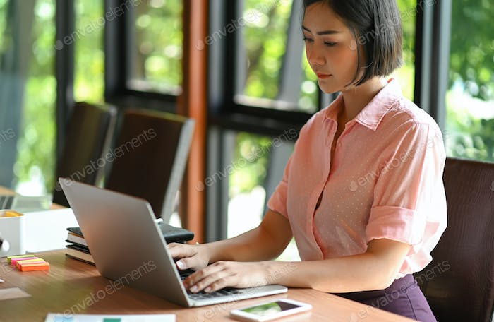 Asian teenage woman is using a laptop in office.