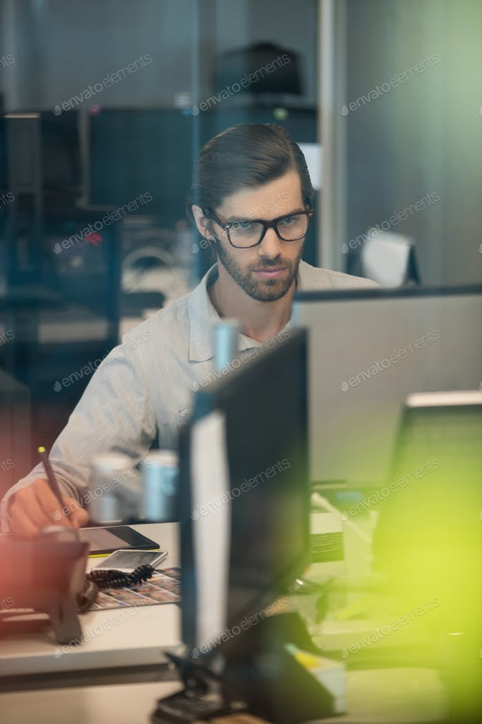 Concentrated businessman working on digitizer in office