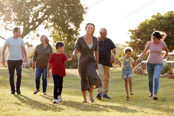 Multi-Generation Family Walking In Countryside Against Flaring Sun