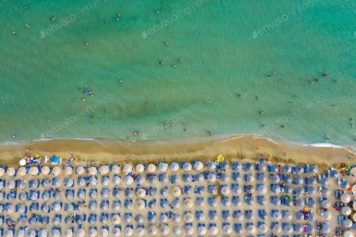 Vista aérea en la playa de arena. Paraguas, arena y paisaje de olas del mar.