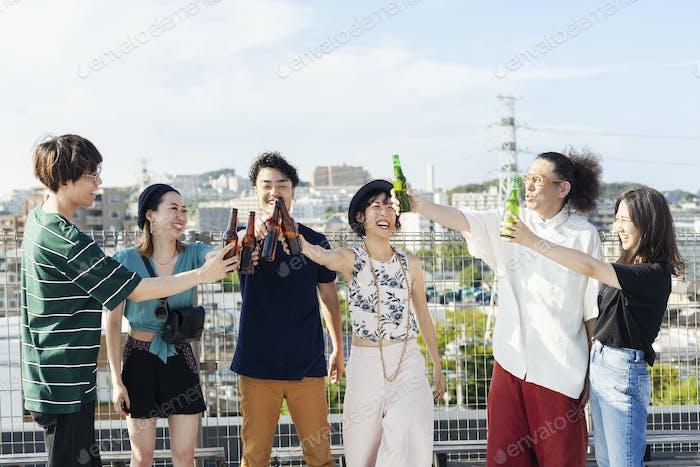 Gruppe junger japanischer Männer und Frauen, die auf einem Dach in einer städtischen Umgebung stehen, Bier trinken.