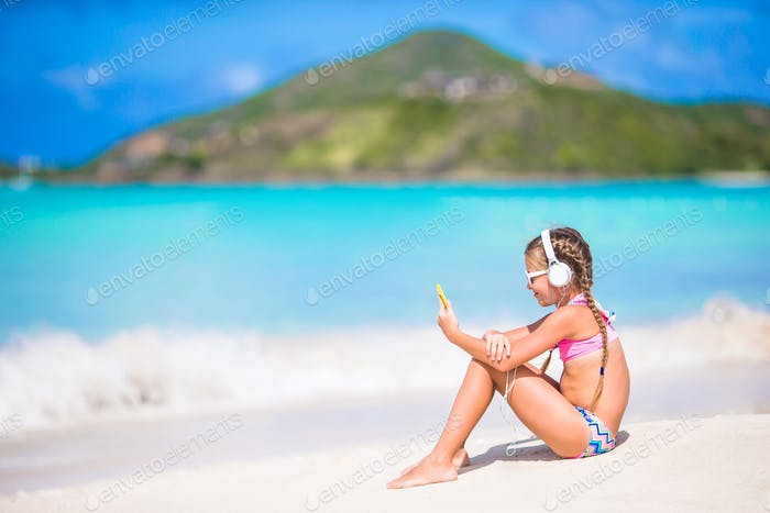 Little girl listening to music on headphones on caribbean beach