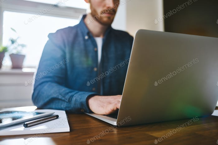 Close up view of man working on laptop