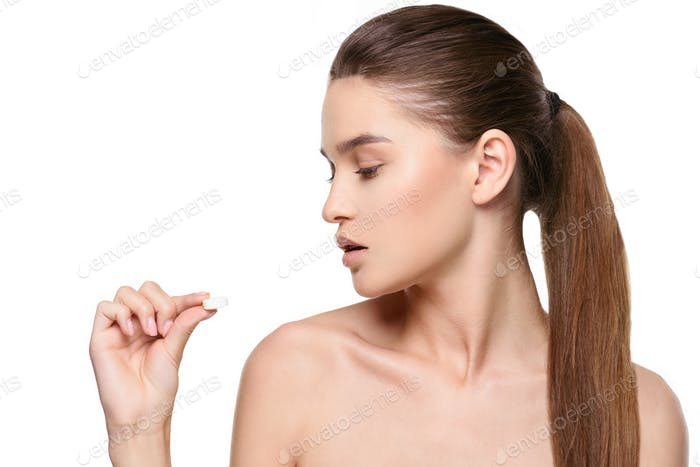 Young beautiful woman holding white pill isolated on white