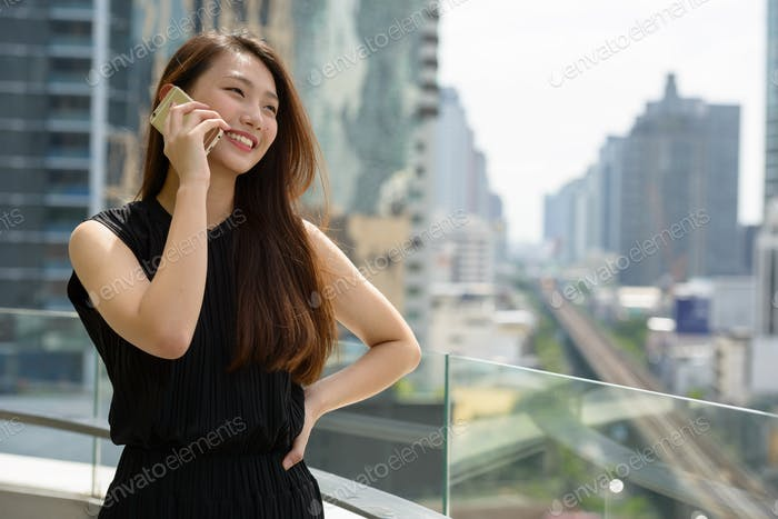 Happy young beautiful Asian businesswoman thinking and using phone against view of the city