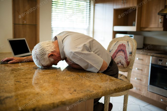 Senior man suffering from heart attack in the kitchen