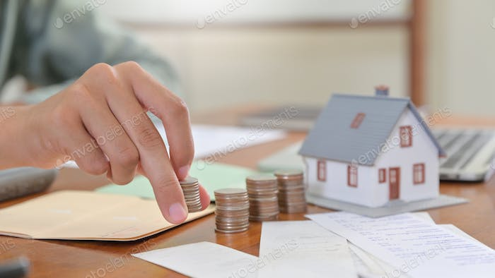Close - up shot of Model house and hand are arranged coins, House buying concepts.