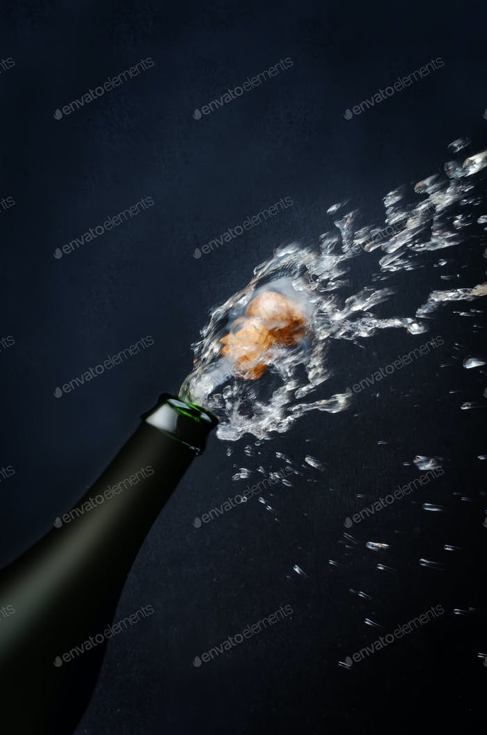 Bottle of champagne with a flying cork and spray