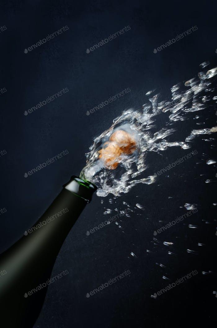 Flasche Champagner mit einem fliegenden Korken und Spray