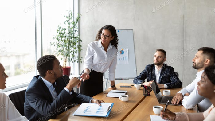 Businesswoman On Business Meeting Talking With Colleagues Standing In Office