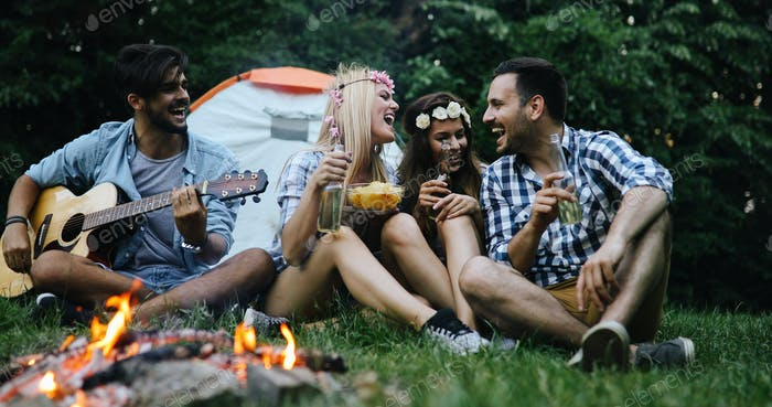 Glückliche Freunde spielen Musik und genießen Lagerfeuer