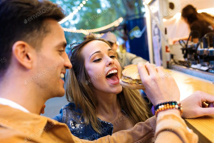 Attractive young man giving hamburger to his beautiful girlfriend in eat market in the street.