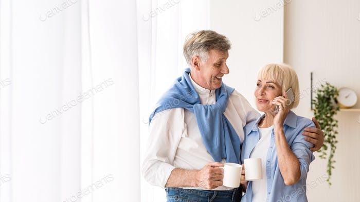 Happy senior woman talking on phone near window, free space