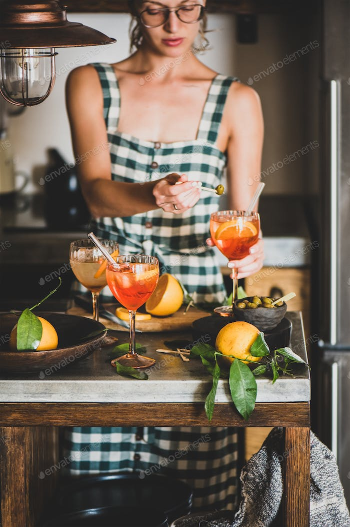 Young woman holding Aperol spritz cocktail and olive
