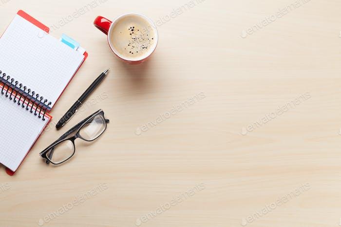 Schreibtisch mit Kaffeetasse, Notizblock und Gläsern