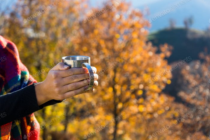 Woman's hands holding a cup of coffee, forest background